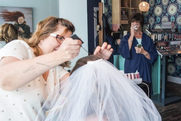 The bride getting her veil put on as her mother looks on in tears at the Foxy Moon Hair Salon in Halifax.