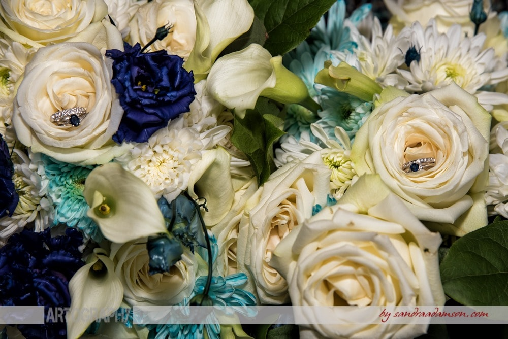 A gay wedding, ivory and navy bridal bouquet with sapphire wedding bands.