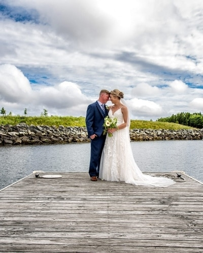A bride and groom posing on a wharf overlooking the Halifax harbour for wedding photos at the Dartmouth Yacht Club.