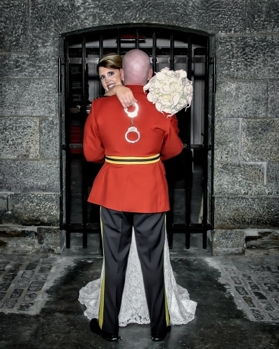 A bride hugs her RCMP groom holding handcuffs at Alexander Keiths Bewery.