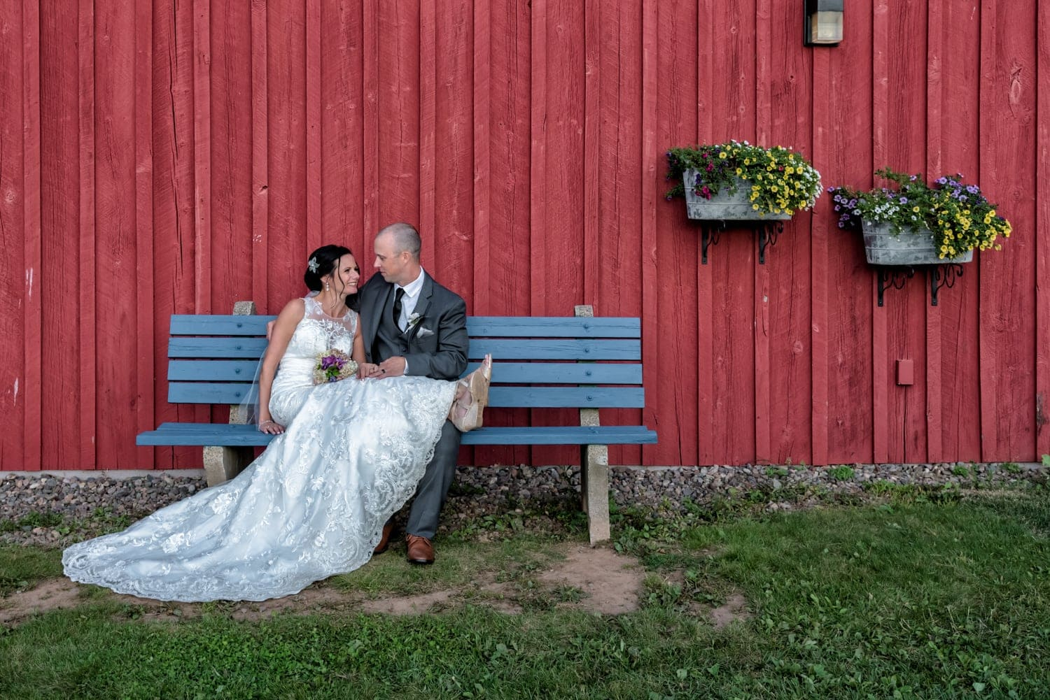 The bride and groom sitting on a wooden blue bench against the Heritage Barn at the Old Orchard Inn, Wolfville NS.