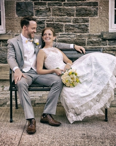 The bride and groom sitting on a rod iron bench at the Historic Properties in Halifax NS for wedding photos.