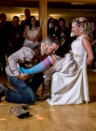 Bride and groom during the wedding garter toss at their wedding reception at the Salmon River Fire Brigade in Nova Scotia.