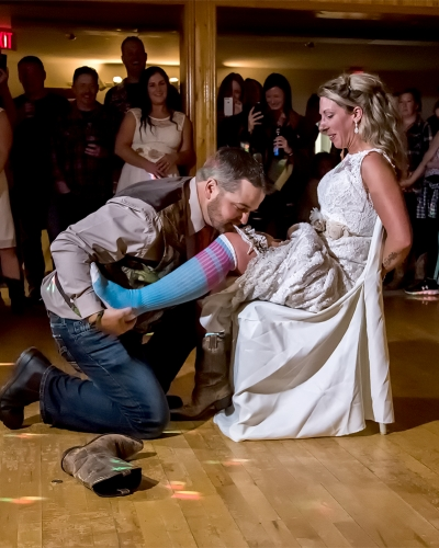 Bride and groom during the wedding garter toss at their wedding reception at the Salmon River Fire Brigade in Nova Scotia
