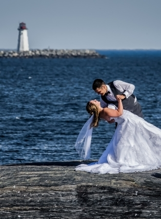 Wedding photography of bride and groom at Point Pleasant Park with lighthouse in the background.