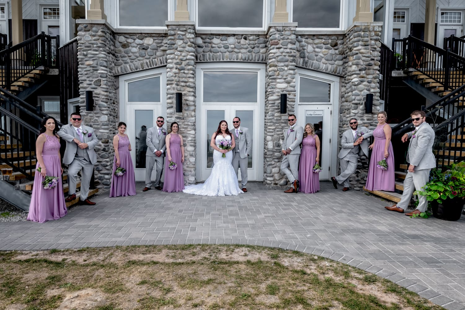 The bride and groom wedding party photos against the White Point main stone building in Nova Scotia.