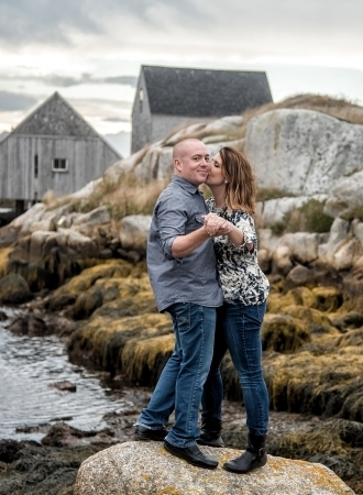 A love couple having their engagement photos done at Peggys Cove in Nova Scotia.