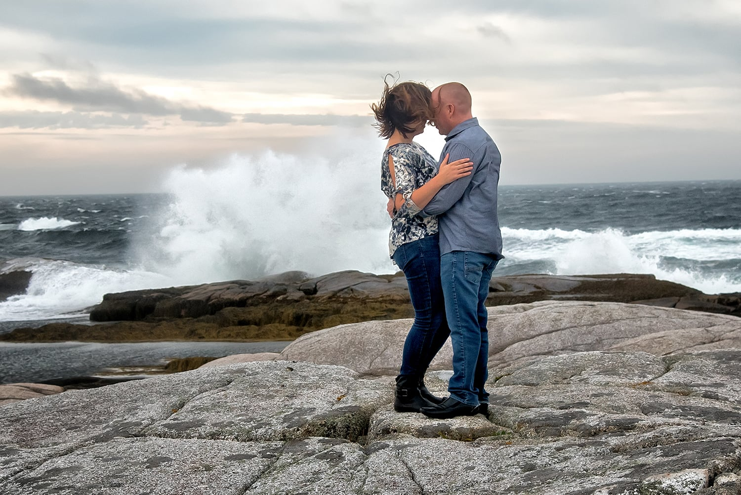 A cute couple embracing for their engagement photos at Peggys Cove in Nova Scotia.