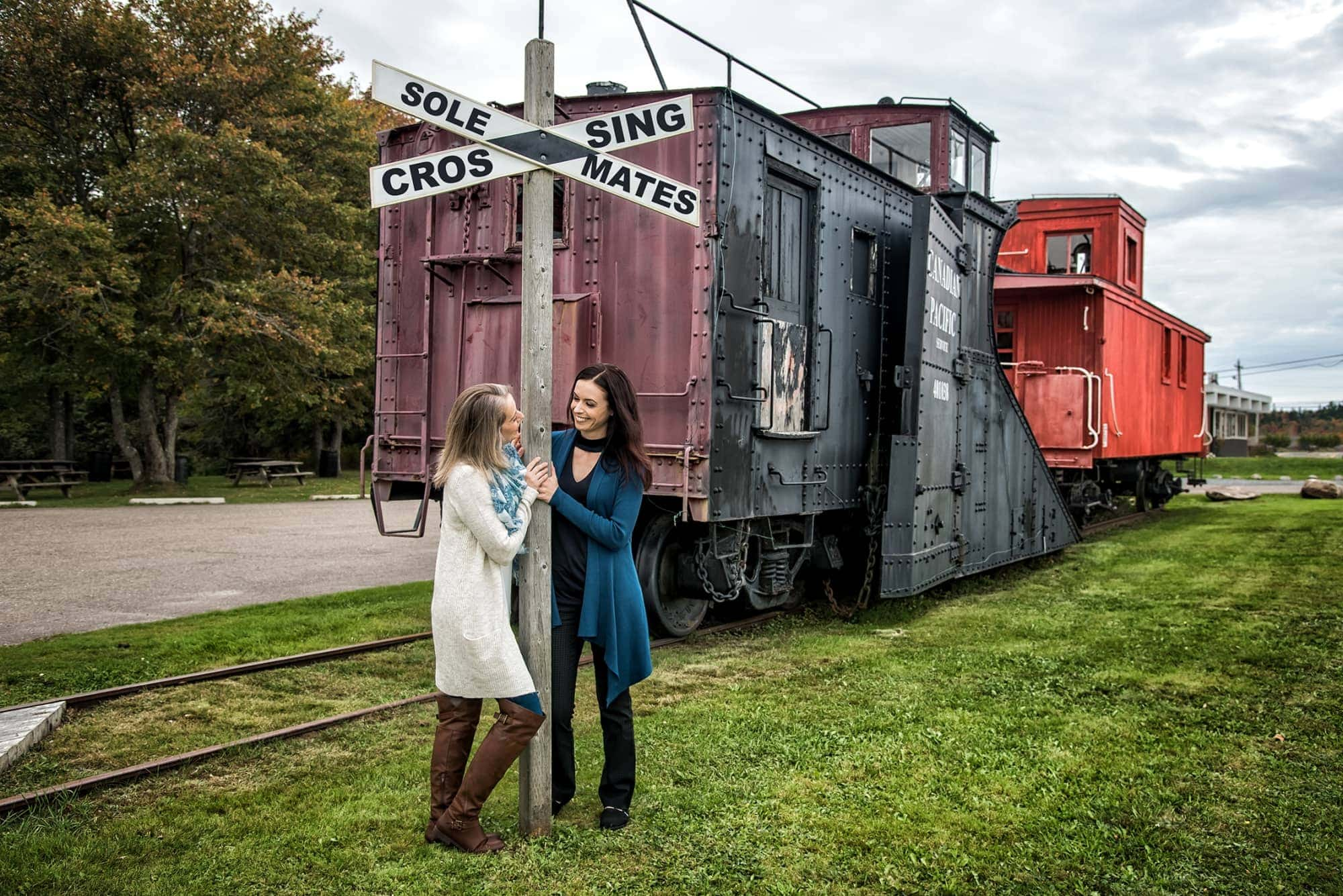 An LGBT lesbian couple stare at each other during engagement photos at the Musquodoboit Train Museum in Nova Scotia.