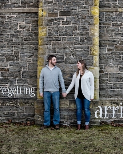 A couple hold hands against the gatehouse in Point Pleasant Park in Halifax, NS.