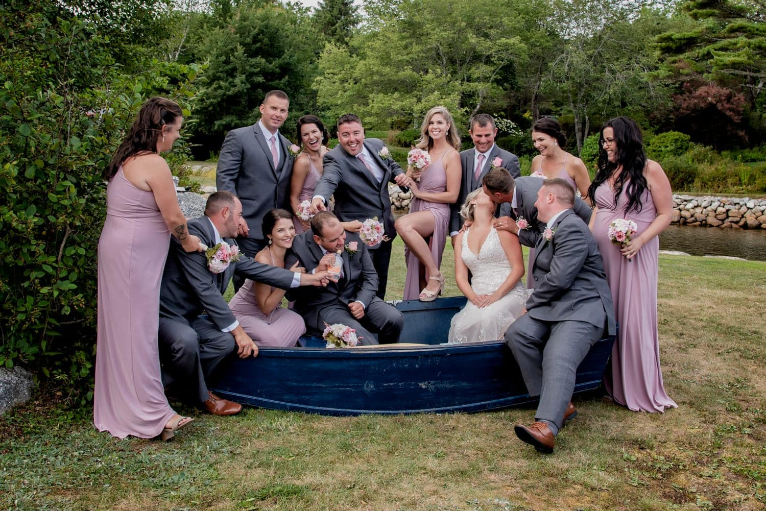 funny wedding party photos with bride and groom in a boat during a backyard wedding in Halifax