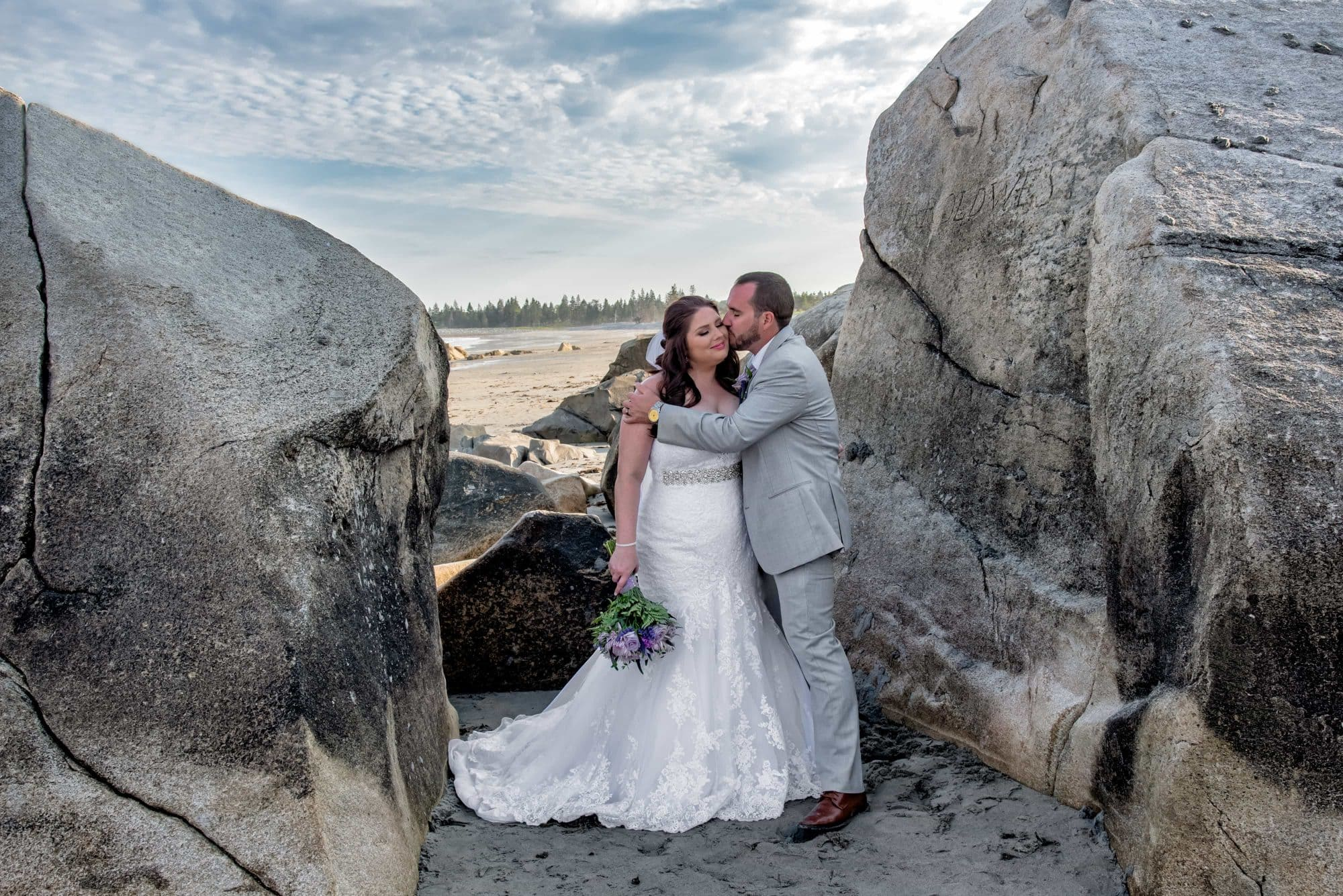 A candid bride and groom photos done on the beach between the rocks during a White Point wedding.