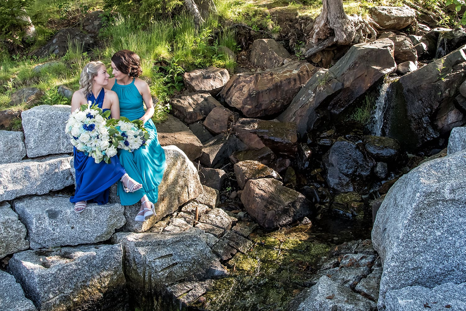 beautiful lgbt lesbian wedding photos at the dingle tower park in Halifax with both brides by a waterfall