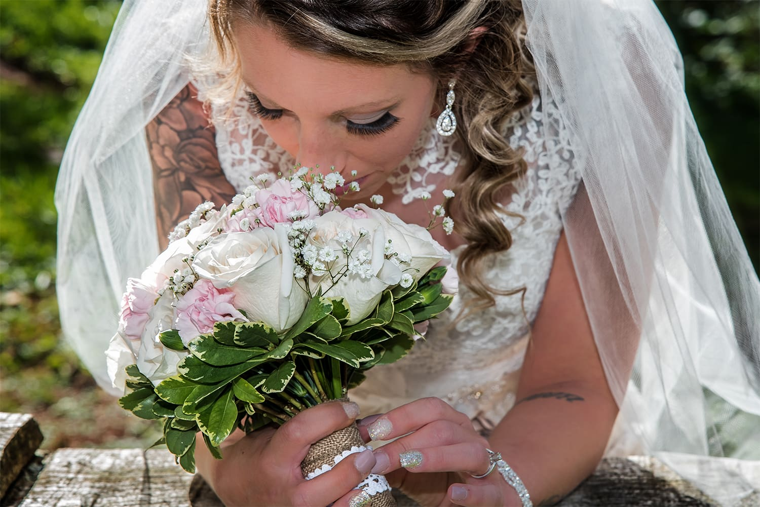 bride in a candid moment smelling her rose floral bridal bouquet