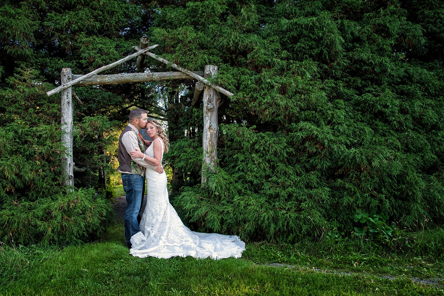 bride and groom holding each other in each others arms among the evergreens at the Rock Garden Park in Bible Hill Truro NS