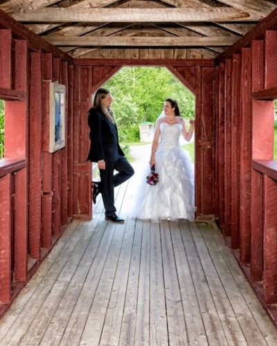 A bride and groom posing for rustic barn style wedding photos in Sackville Waterfowl Park in NB.