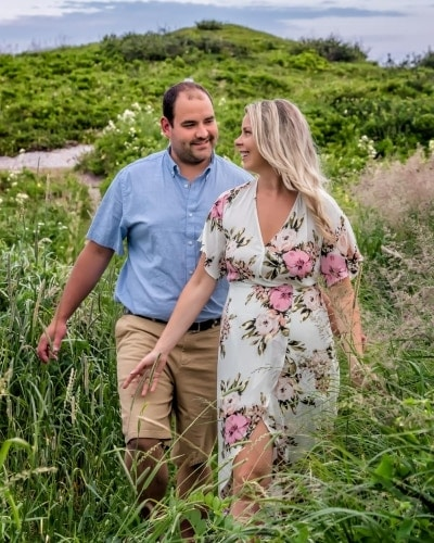 A cute couple walk among the high grass during an engagement shoot at Sandy Cove, NS.