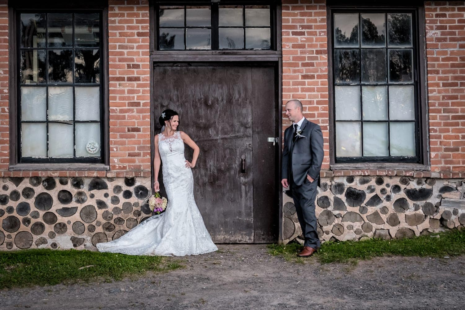 The bride and groom wedding photos, they are standing against the wooden doors of an urban brick style building at the Old Orchard Inn.