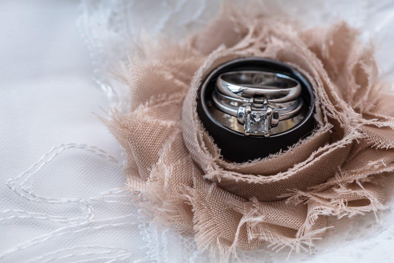 The wedding rings inside an ivory flower on the wedding garter belt.