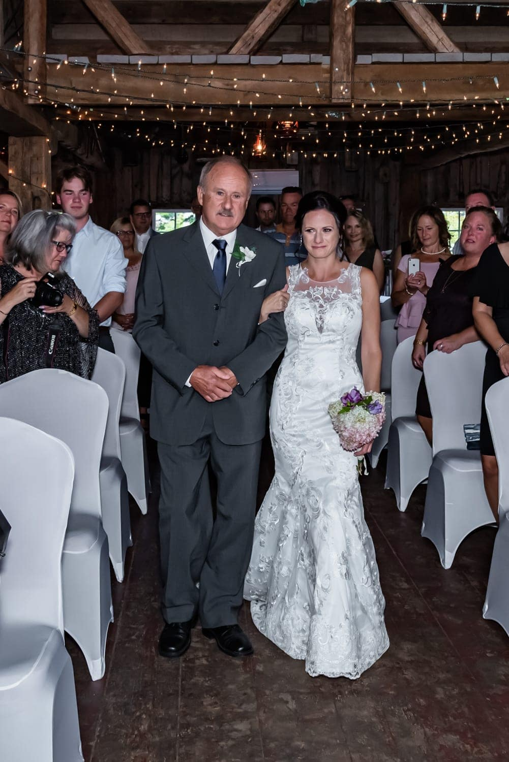 The father of the bride walking her up the aisle at the Old Orchard Inn Heritage Barn.