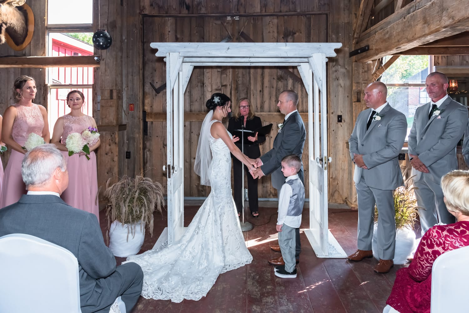 The bride and groom under the wedding arch during their wedding ceremony at the Old Orchard Inn.