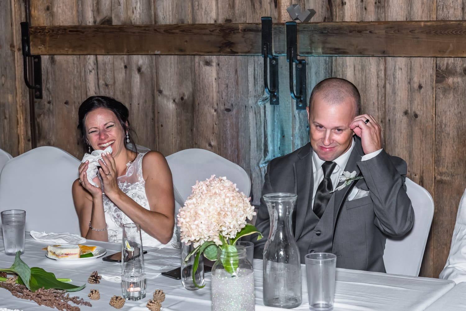 The bride and groom laughing at their wedding speeches during their wedding at the Old Orchard Inn.