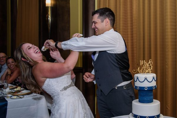 The groom shoving the wedding cake into the bride's face at a Juno Tower Halifax wedding.