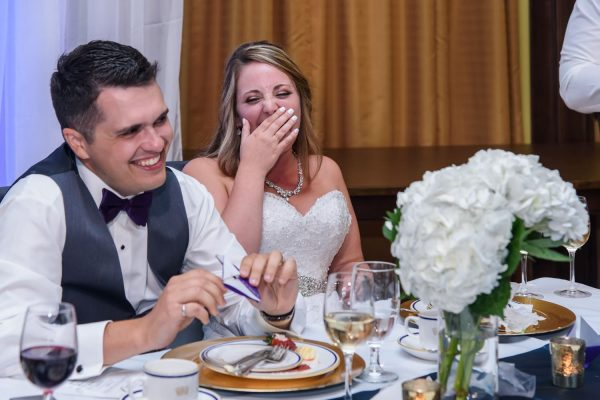 The bride and groom laughing during the wedding speeches at Juno Tower in Halifax.