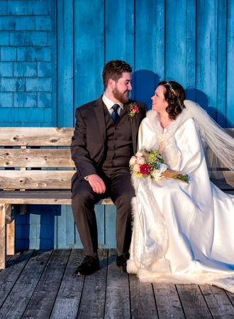 The bride and groom sitting on a wooden bench at Fishermans Cove in Eastern Passage.