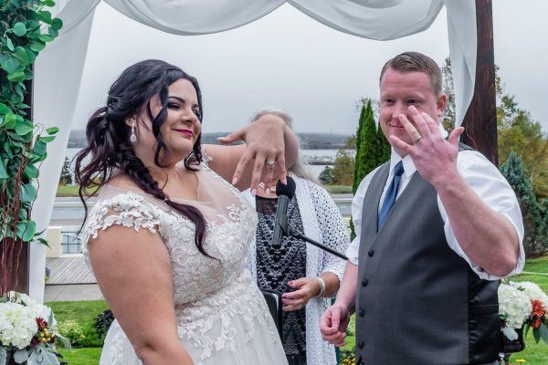 The bride and groom showing off their wedding rings during their ceremony at Digby Pines.