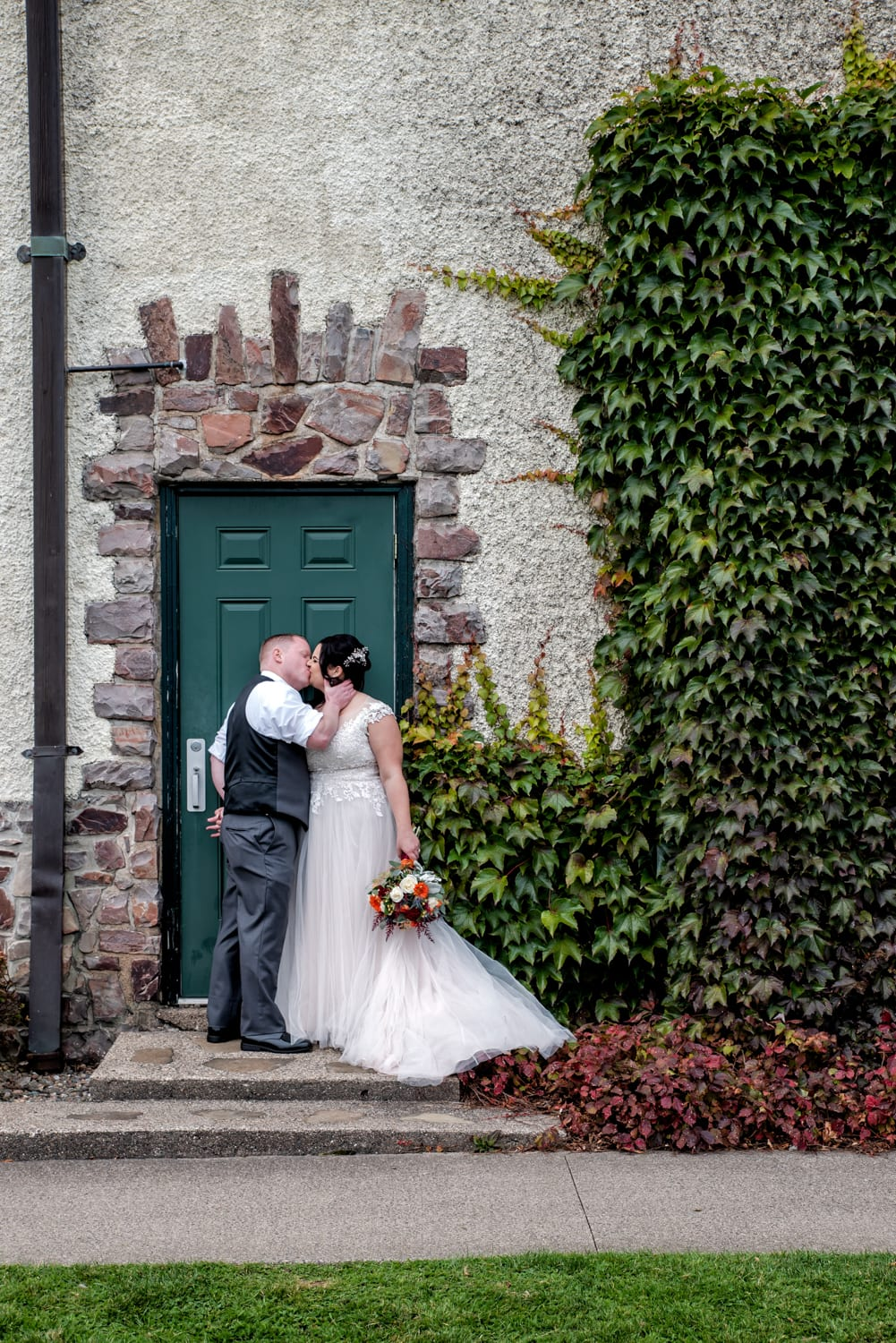 The bride and groom kiss against a stone and brick wall with veins, during their wedding photos at Digby Pines.