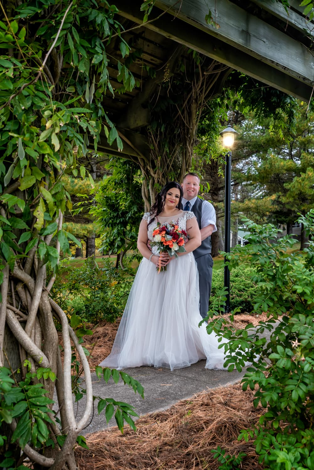 A bride and groom standing under an archway of veins at Digby Pines.