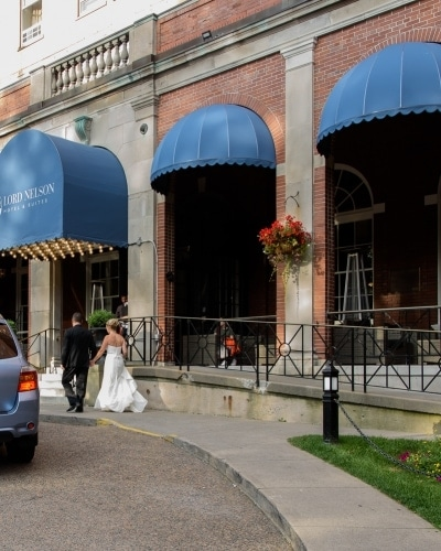 The bride and groom walking outside the front of their hotel l in Halifax, NS.