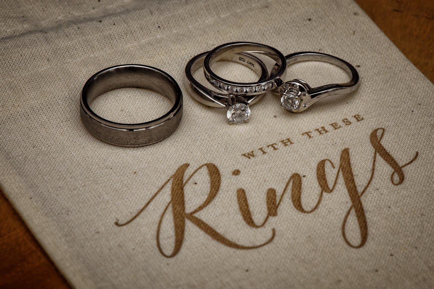 The bride and groom wedding bands on a cute with this ring we thee wed ivory burlap bag.