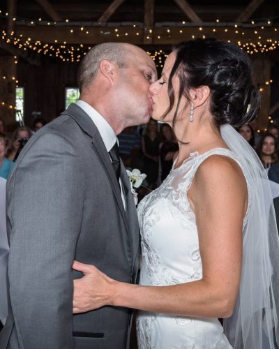 The bride and groom share a first kiss during their barn wedding ceremony in Wolfville NS.
