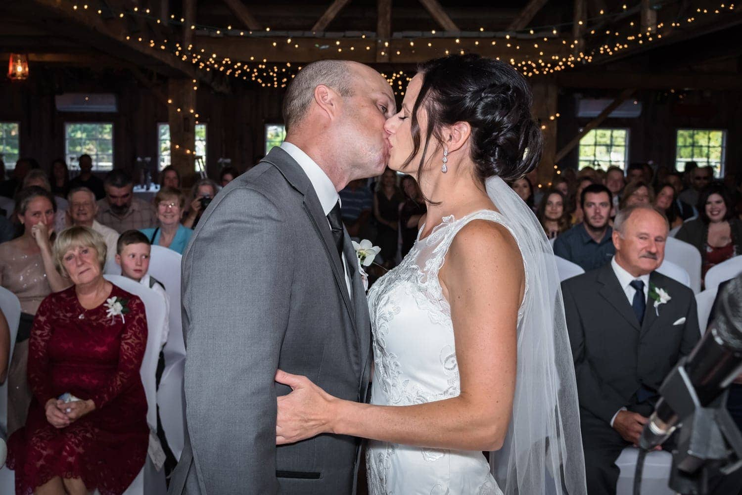 bride and groom share a first kiss during their barn wedding ceremony at the Old Orchard Inn