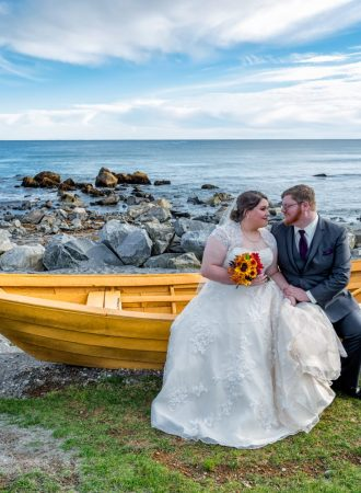 Wedding photos of the bride and groom in a yellow boat at white point beach resort.