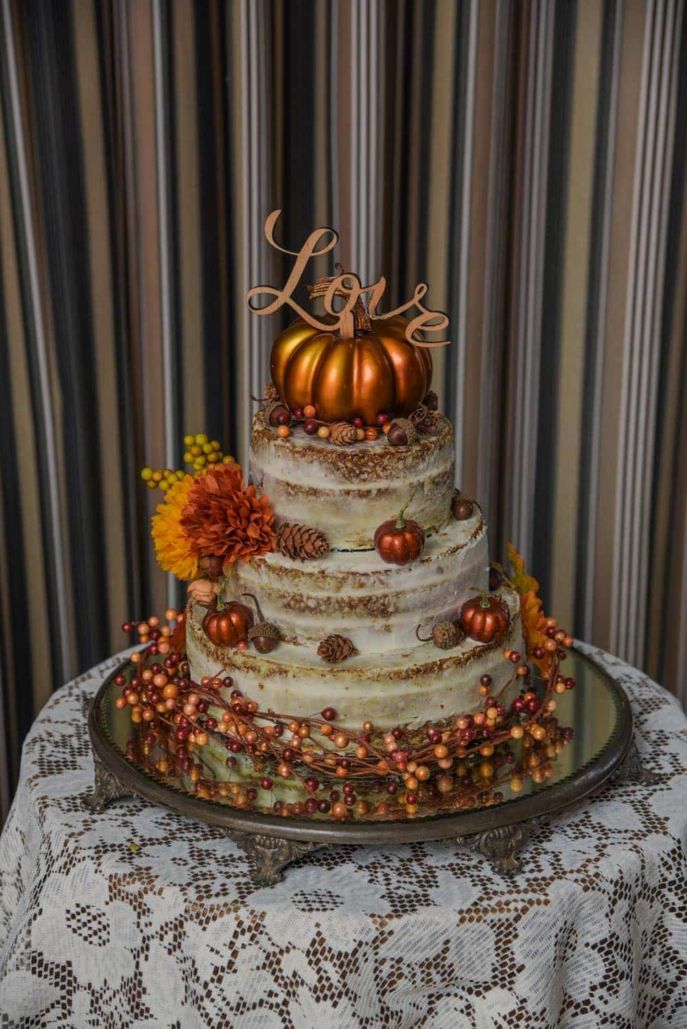 A 2 tier autumn themed wedding cake with pumpkins and love wedding cake topper at a White Point wedding.