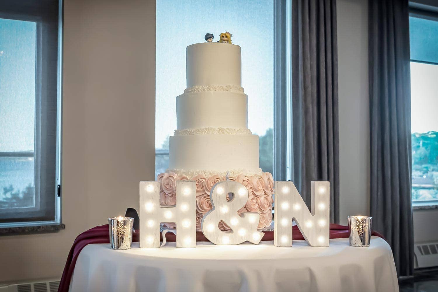 A 4 tier wedding cake with figurine wedding cake toppers and marquee letters lit up at the Bedford Basin Market.