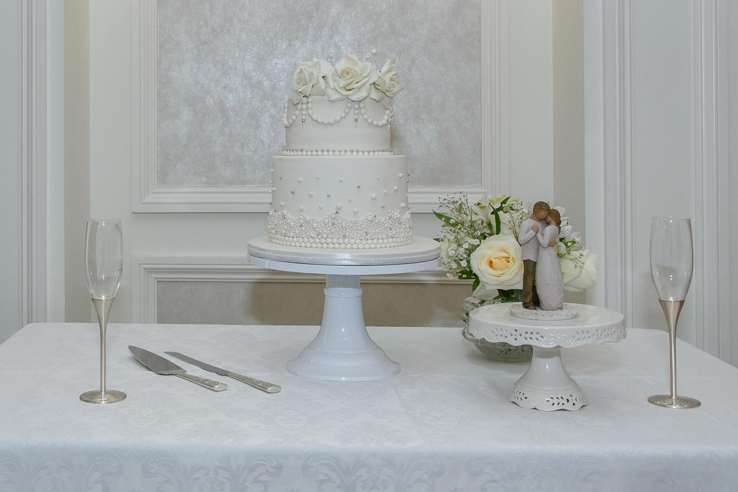 An elegant ivory wedding cake with bride and groom figurine at a Lord Nelson Hotel wedding.