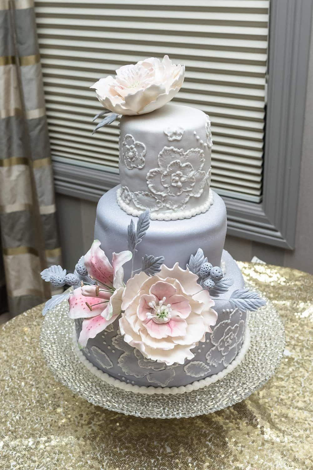 A 3 tier wedding cake with flower wedding cake toppers at an Ashburn Golf Club wedding.