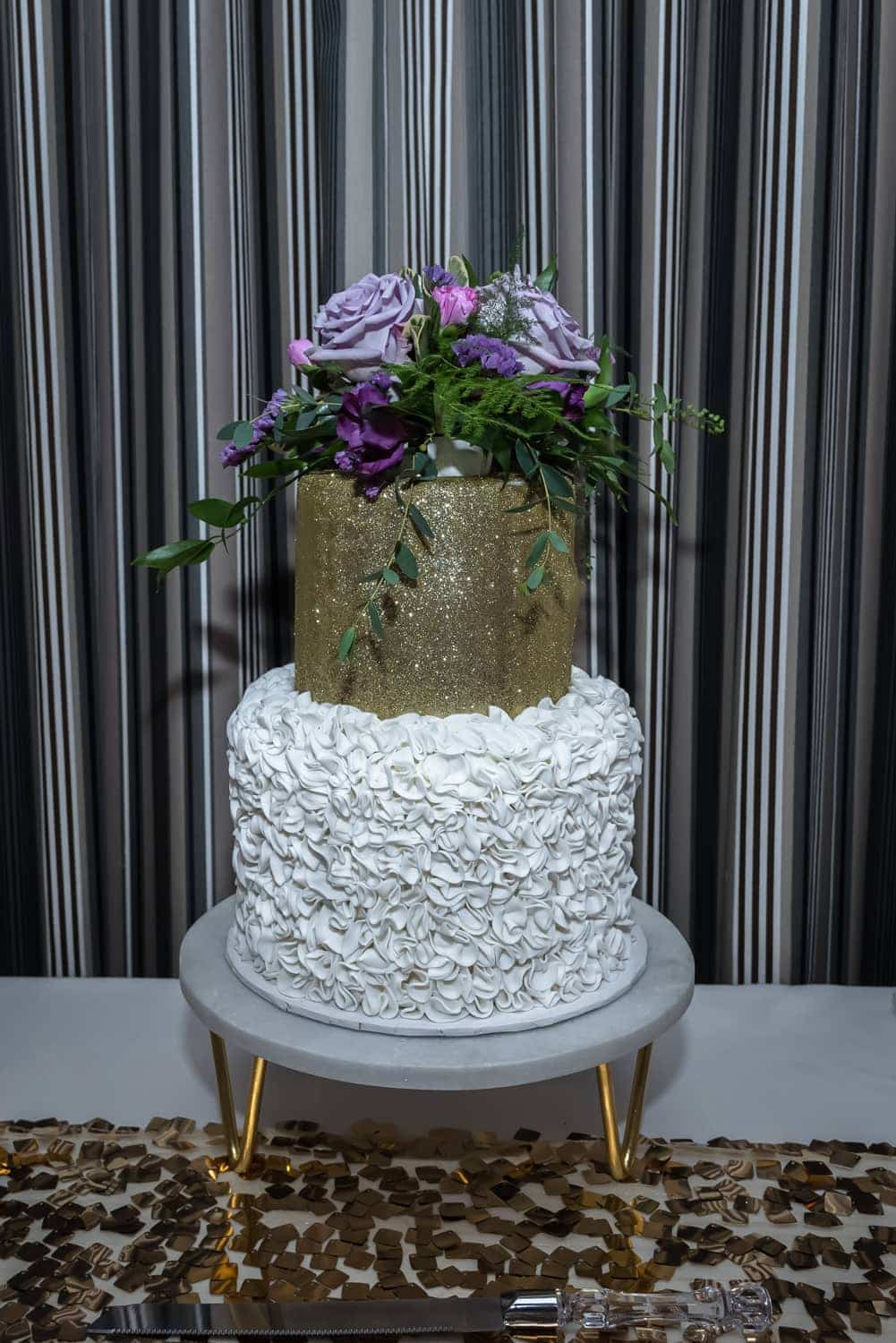 A gold fondant 2 tier wedding cake with floral wedding cake toppers at a White Point Beach Resort wedding.