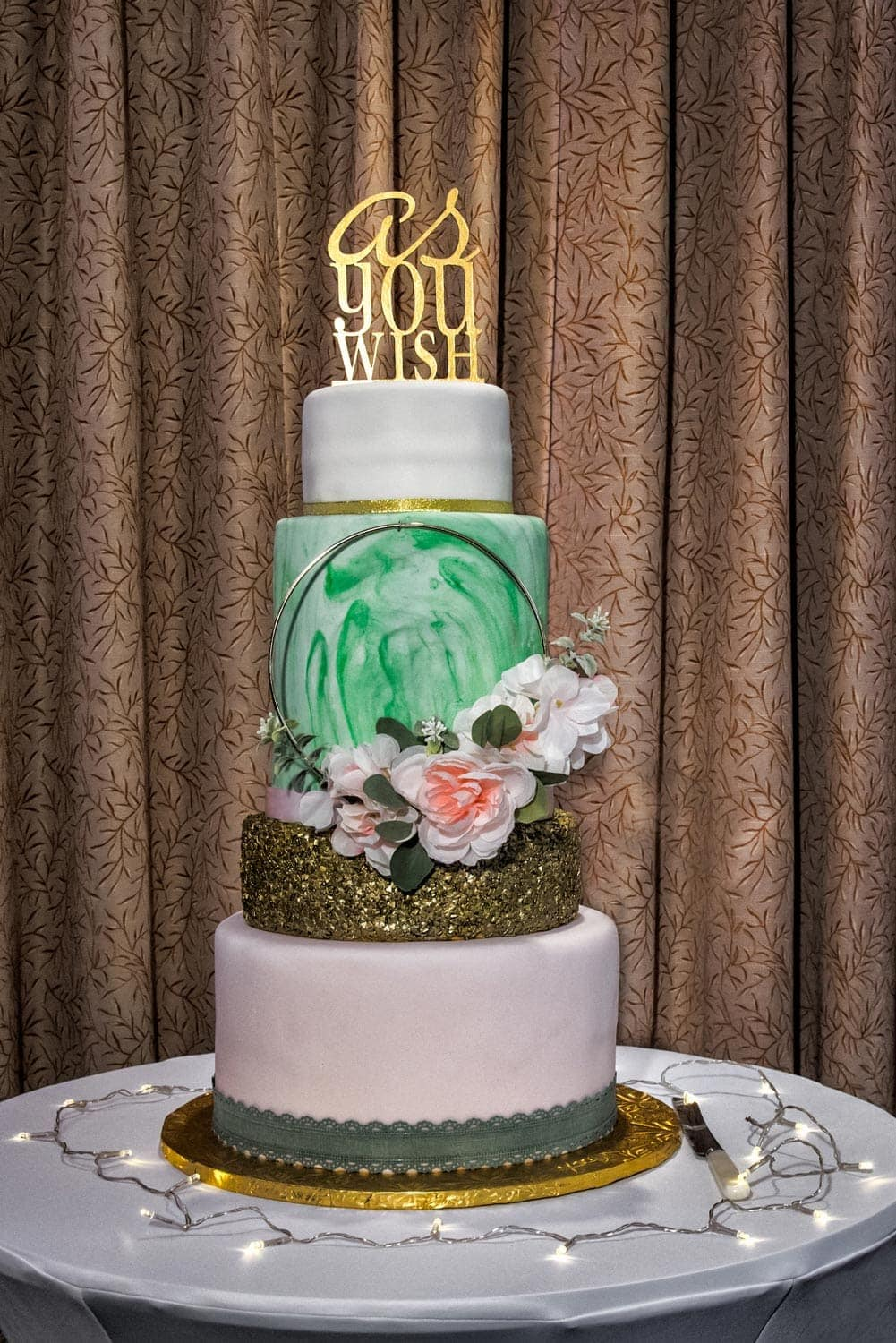 A 4 tier wedding cake with gold wedding cake topper designed by the bride at a Best Western Chocolate Lake wedding.