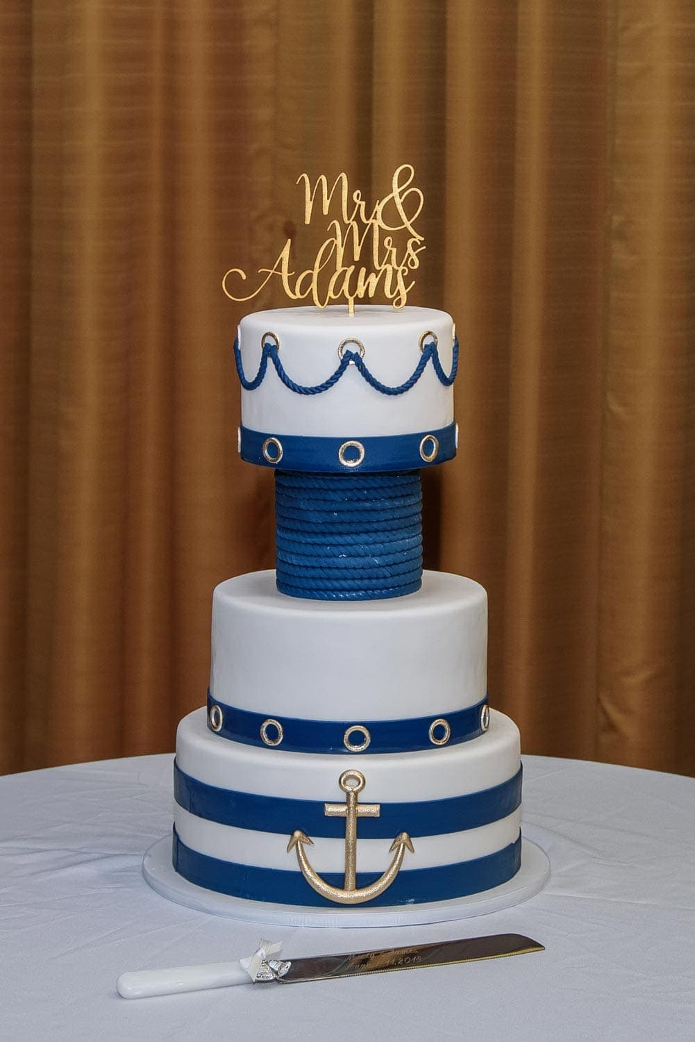 A nautical sea themed wedding cake with gold mr and mrs wedding cake topper at a Juno Tower Halifax wedding..