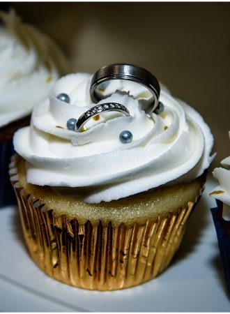 The wedding rings in the icing of a wedding cupcake.