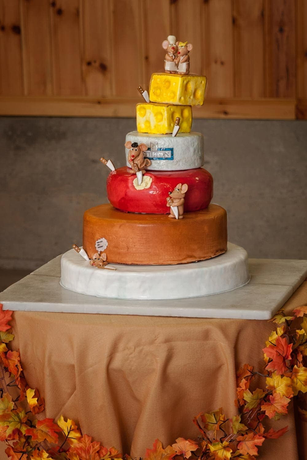 A 5 tier cheesecake themed wedding cake with mice on each level.