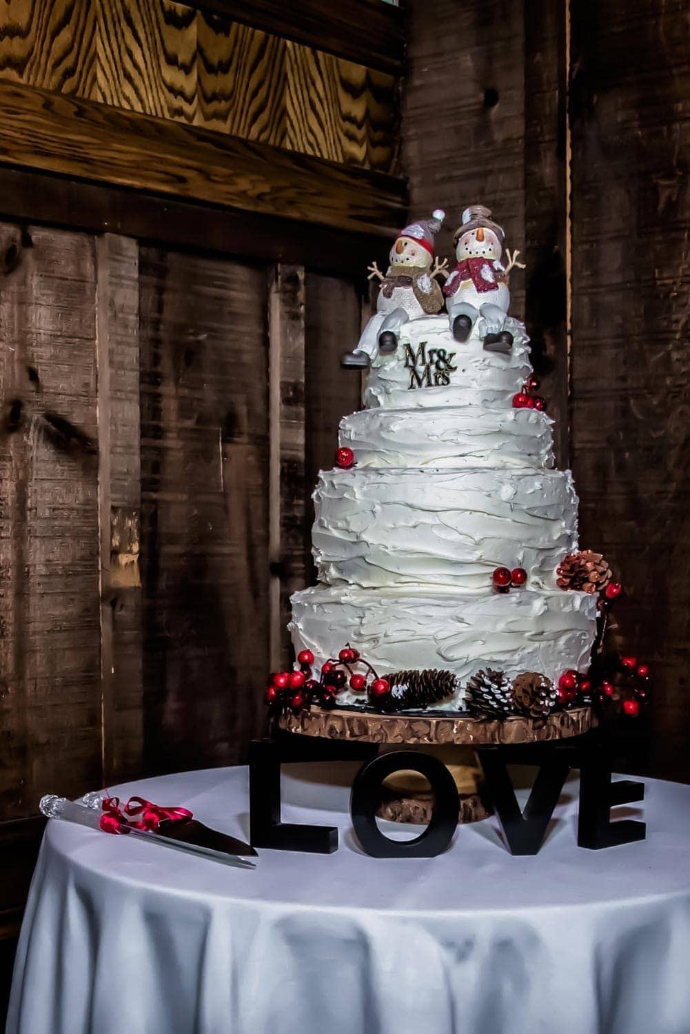An awesome winter themed wedding cake with snowman wedding cake toppers at a Lower Deck Tap Room wedding.