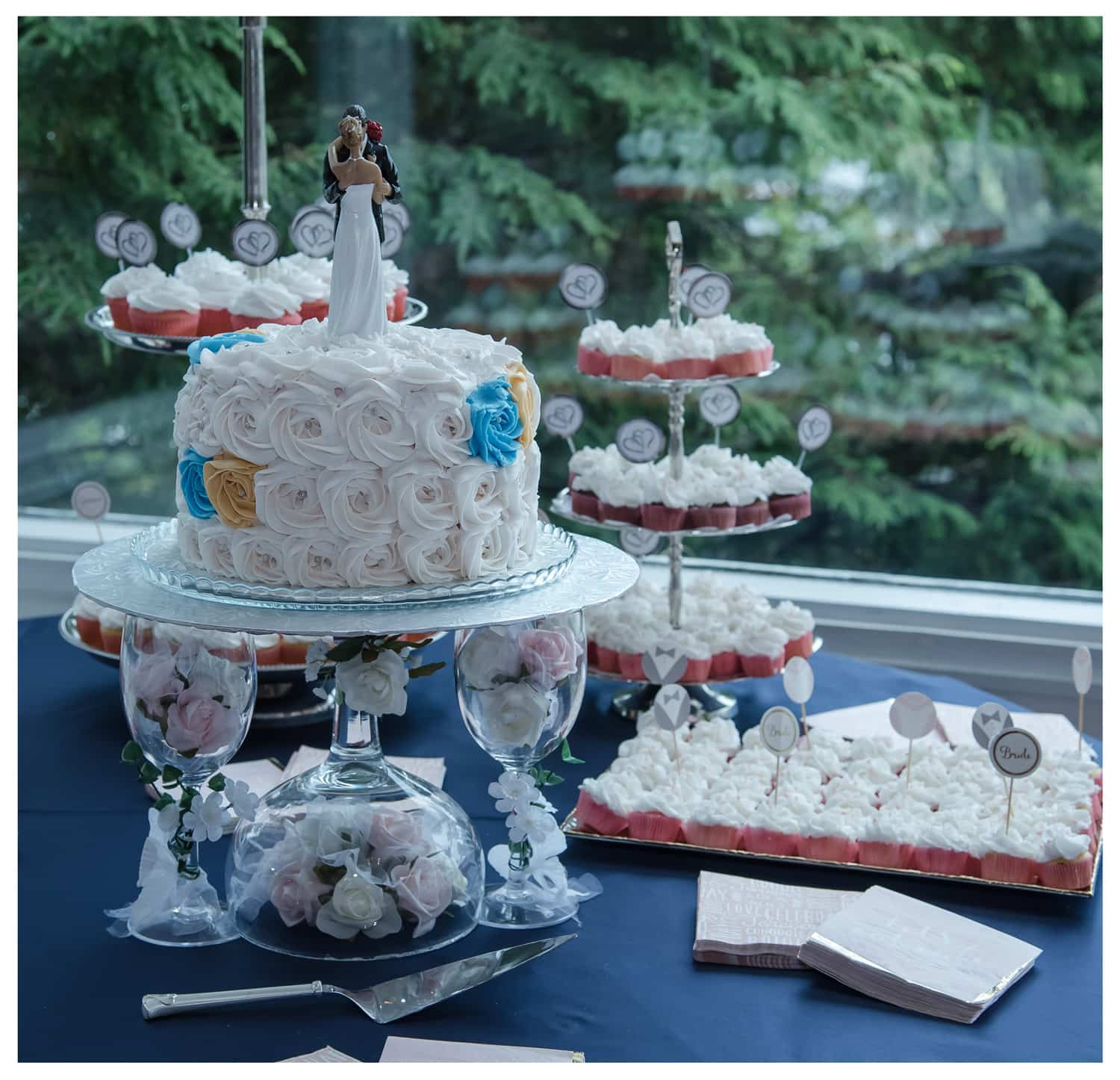 a single tier wedding cake with a bride and groom wedding topper figurine surrounded by wedding cupcakes on a cupcake stand