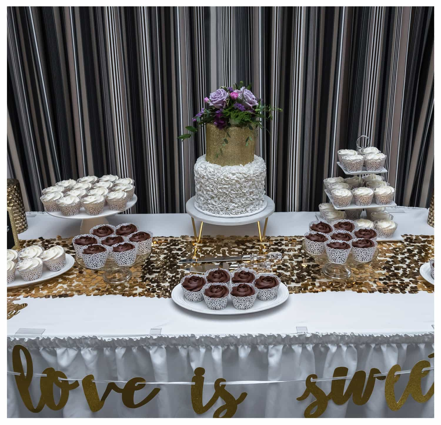 a two tier wedding cake with floral wedding cake topper surrounded by wedding cupcakes on three tier cupcake stands