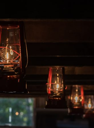 Lit lantern wedding decorations in the heritage barn at the Old Orchard Inn.